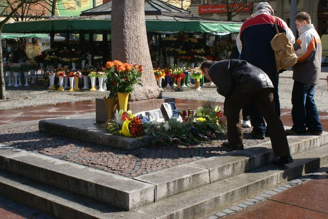 Na pl. Solnym położono zdjęcia prezydenckiej pary. Obok nich mieszkańcy miasta składają kwiaty i znicze.